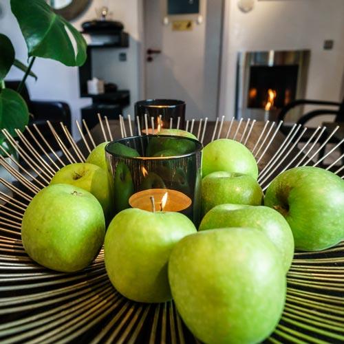 Schale mit Äpfeln und Kerze